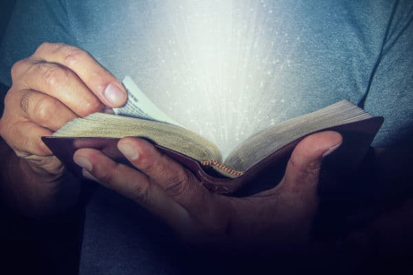 Man turning pages of Bible with light coming from pages.